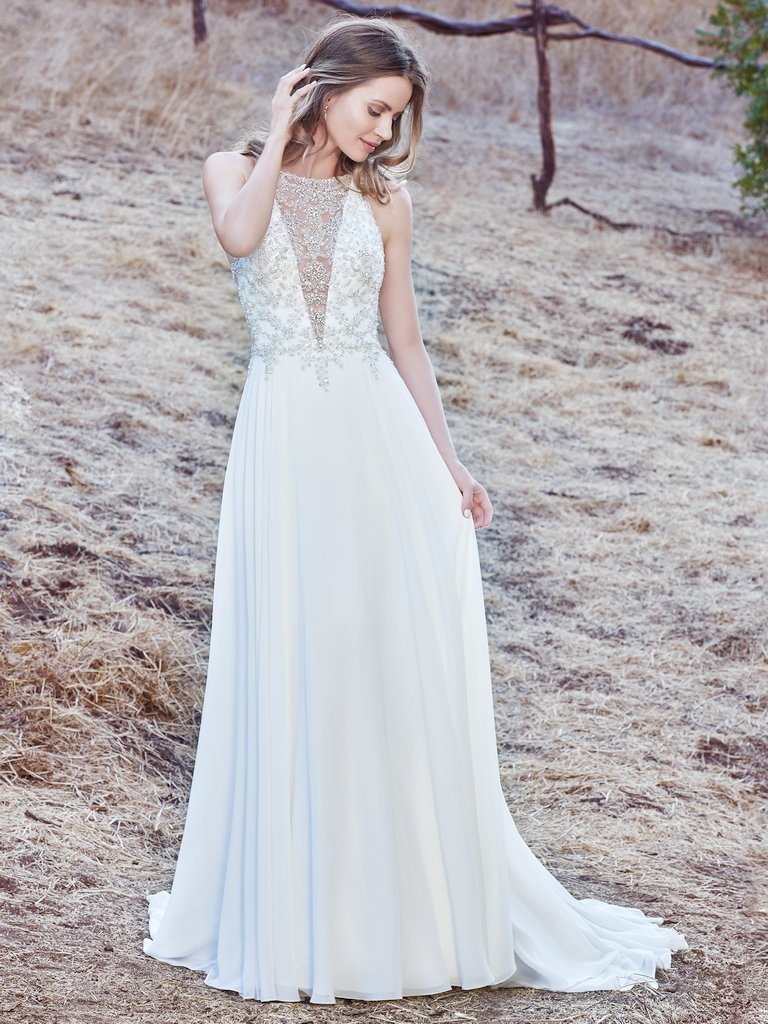 Maren -  This sleeveless sheath wedding gown features a bodice accented in Swarovski crystals and delicate beading, creating an illusion jewel over deep V-neckline and illusion open back. A Revina Chiffon skirt completes the elegant romance of this look. Finished with crystal buttons over zipper closure.     Colors Available - Ivory