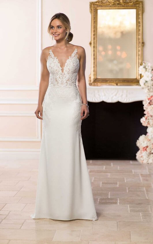 6648 -  Modern meets sexy in this sleek silhouette by wedding dress designer Stella York. Matte lace and silky crepe create a sheath silhouette with plunging V-neckline and naked illusion back. The sheer V-shaped bodice is created by matte lace with an organic finish that adds a botanical look to the lace.     Available in -