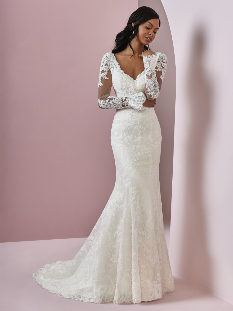 Bonnie -  A unique take on the sleeved wedding gown, this tulle fit-and-flare features illusion bell sleeves accented in lace motifs. Soft lace motifs adorn the bodice, illusion V-neckline, and illusion scoop back. Finished with covered buttons and zipper closure.    Available in Ivory and Ivory over Pearl