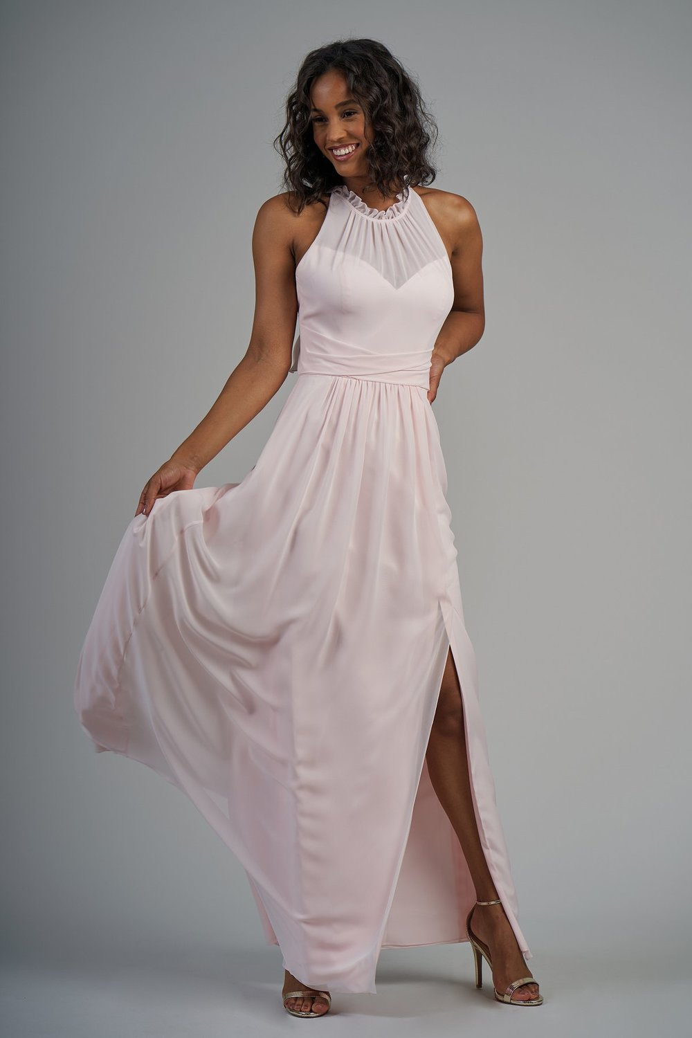 B213002 -  Beautiful poly chiffon floor length bridesmaid dress with a ruffled jewel neckline and gathers on the bodice. Pretty ruffle details on the back bodice, detailed gathers on the skirt, and a front slit to complete the look.   Available in 56 Colors