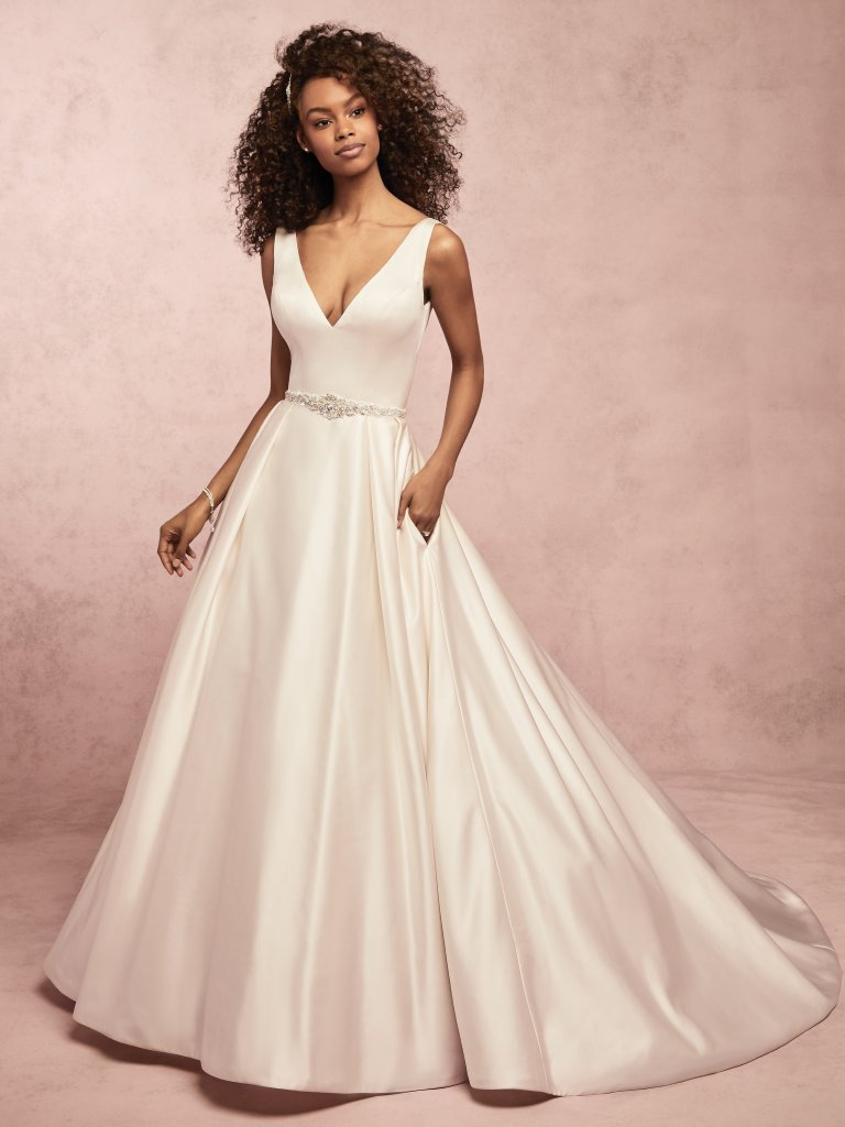 Sammie -  This simple yet romantic Soft Shimmer satin wedding dress features a billowing ballgown skirt, with chic straps completing the V-neckline, V-back and pockets. Finished with covered buttons over zipper closure. Beaded belt accented in Swarovski crystals sold separately.    Available in: Diamond White, Ivory