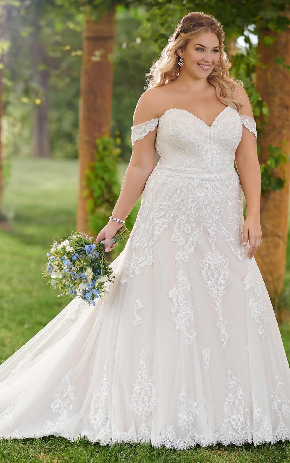 D2525 -  Ideal for a sophisticated soirée, this formal A-line wedding dress from Essense of Australia is classic and romantic. Designed in a modern, A-line silhouette, the bodice of this gown features a sweetheart neckline, highlighted on each side by drapey, off-the-shoulder sleeves. The placed lace of the bodice helps shape the body, and the lace design extends down onto the skirt, finishing off at the hem.    Available in - All White, All Ivory, Ivory/Moscato