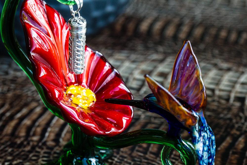 Glass hummingbird sculpture with silver keepsake