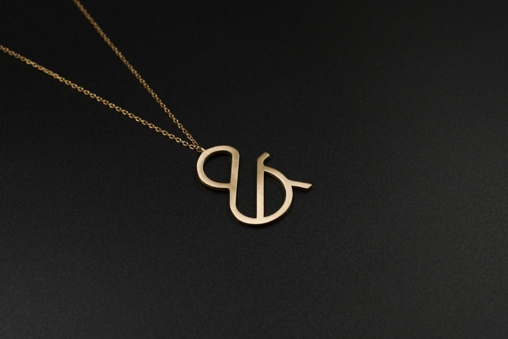 gold ampersand necklace by moshik nadav typography nyc