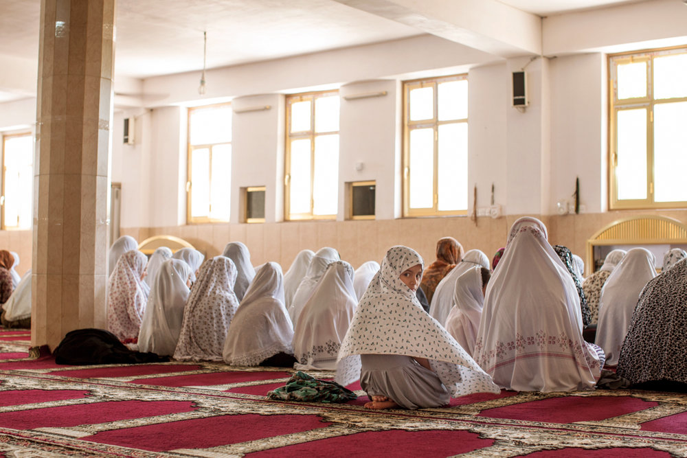 You women listen to an imam upstairs preach over the speaker during Friday prayer in the basement of a mosque in Soran, Iraq (May 2016).