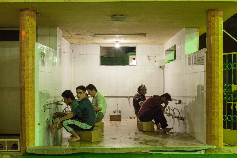 Men wash their feet in preparation for evening prayers at a mosque in Northern Iraq (2016).