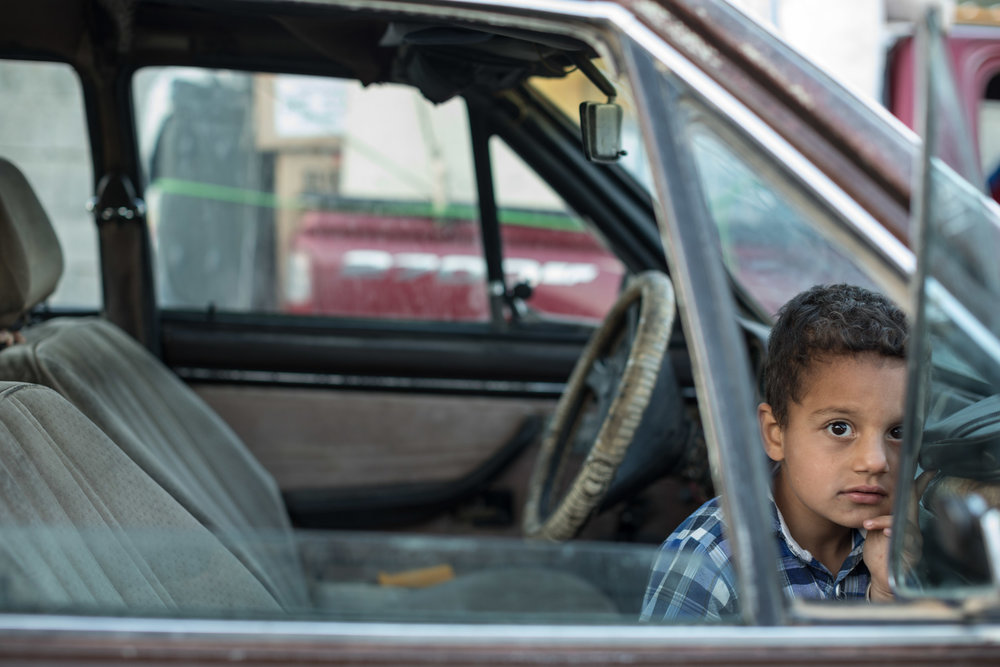 Boy from Mosul, Iraq waits in the car to return home as his parents pack up the shelter they lived in for three years after fleeing ISIS in 2014 (May 2017).