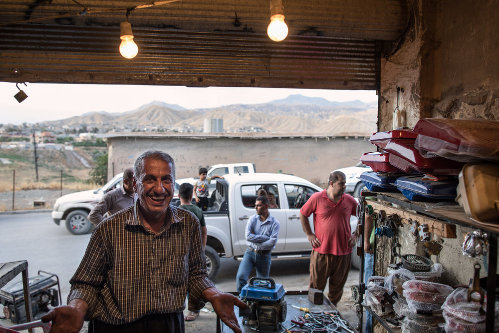 Kudish mechanic inside his garage at dusk. Soran, Iraq (July 2017).