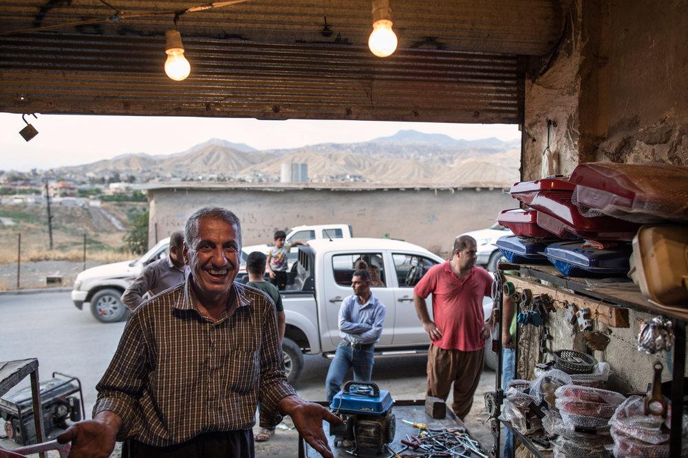 Kudish mechanic inside his garage at dusk--Soran, Iraq (July 2017).