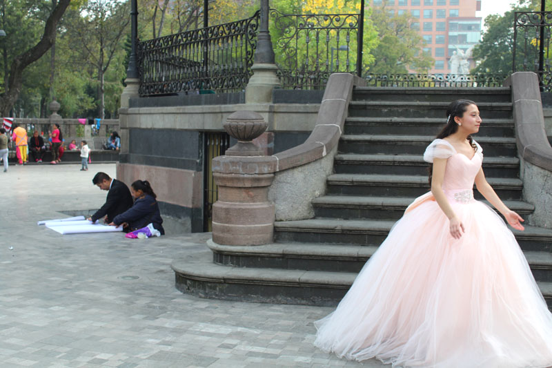 Above: A photo of Cesar under the kiosk in Parque Alameda (in his black suit, on the left, while on the right of him is his wife Lupe) working on his last drawing as he situated himself in a nook of a staircase, indirectly negotiating space with the quinceañera photo shoot that was going on as to avoid interrupting it.
