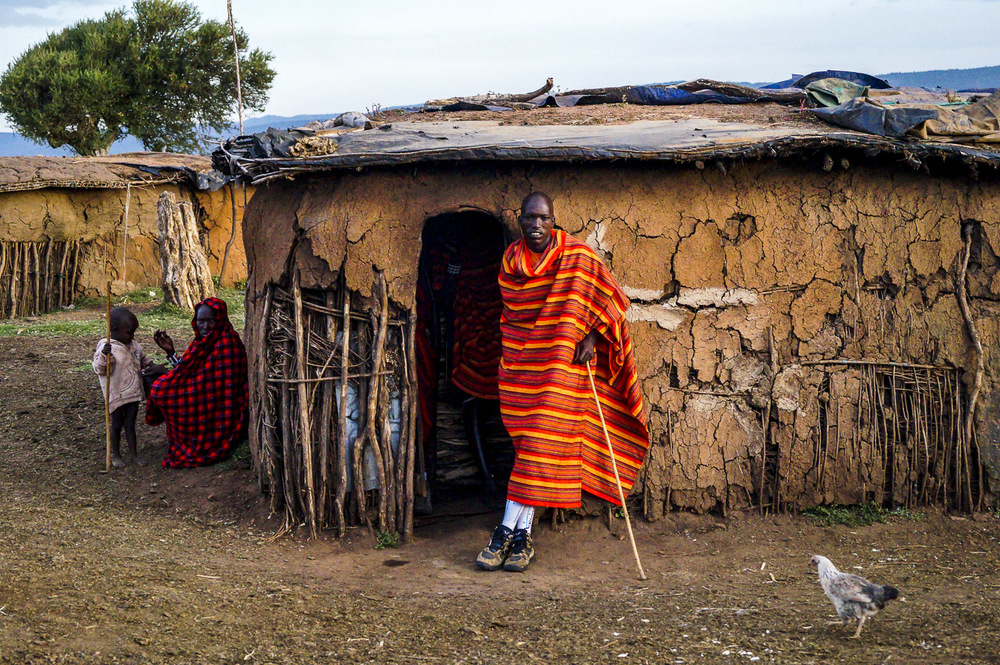 Despite the isolation of these villages, hints of modern society seep in. I love the contrast of the mud houses and traditional Maasai blankets with the moddern socks and sneakers worn by the Maasai man pictured.