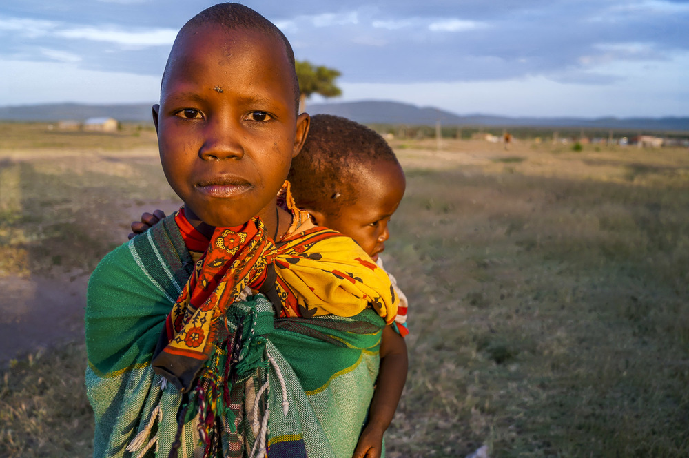Here a young Maasai girl cares for her younger sibling. It is common in a Maasai village to find young girls are responsible for chores such as cooking, milking animals and caring for siblings, skills which they learn from their mothers at an early age.