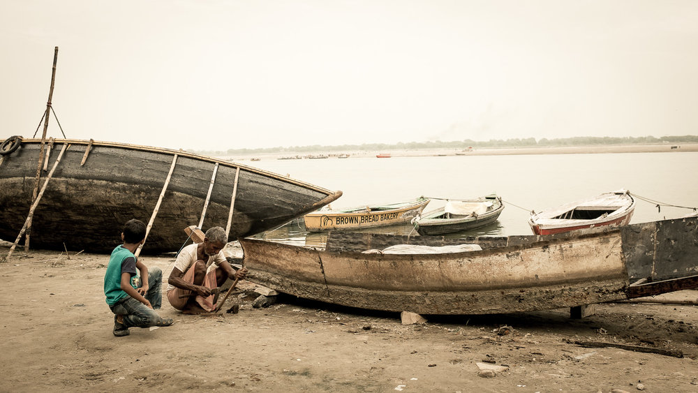 A grandad and nephew are working on a boat. Varanasi, Uttar Pradesh.
