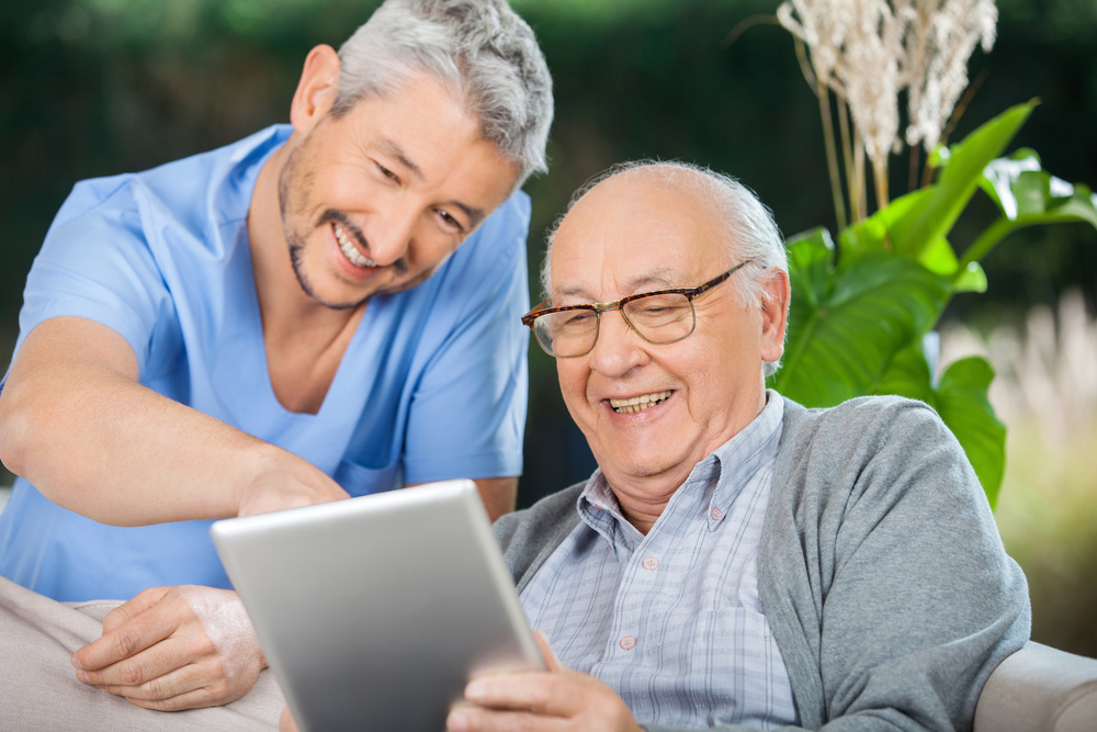 Image of male nurse helping older gentleman with HeraTrack software on tablet.