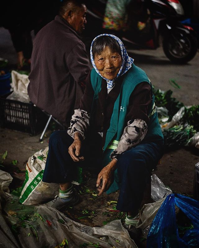 Food markets in China. I know, everyone is curious for crazy fancy food photography and for sure, there will be some of it. BUT actually – for me – the most interesting parts in food markets were the people. Especially this lady: sitting on the floor surrounded by a few vegetables from her garden. I remember how I tried to take a picture of her without talking or gesturing.. so stupid for I never work like that! Actually, this is my biggest capability: connecting with people to capture their little-something in an honest and authentic way. But here in China, I was shy and felt great frustration. Suddenly, at this little hidden food market, something special happened. This lady glanced at me smiling all over her face and SHE captured my heart and I knew: that's it. Without words. I pressed the button. #nowordsneeded #thankful #wanderingphotographer #explorechina #pursuitofportraits