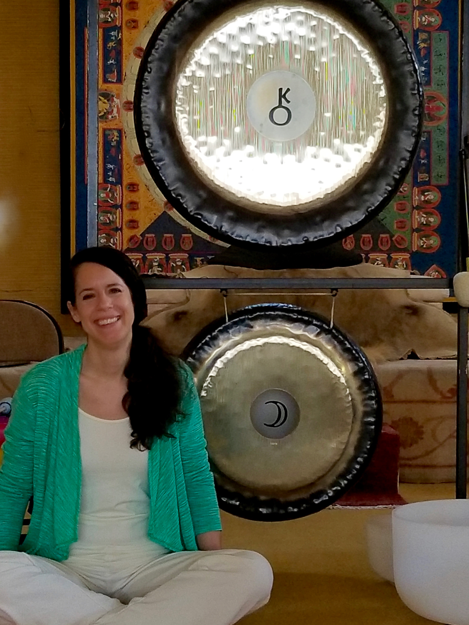 Dr. Michelle Hebert with gong and crystal singing bowl
