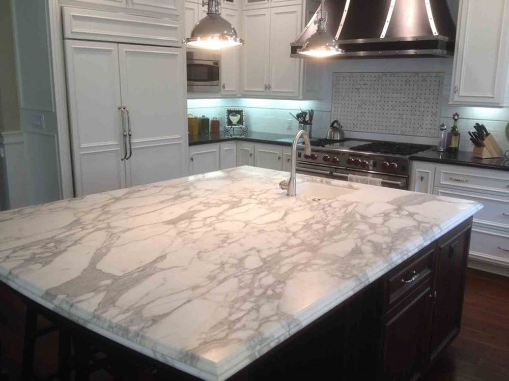 A quartz countertop in a light off-white color with grey veining adorns this kitchen island.