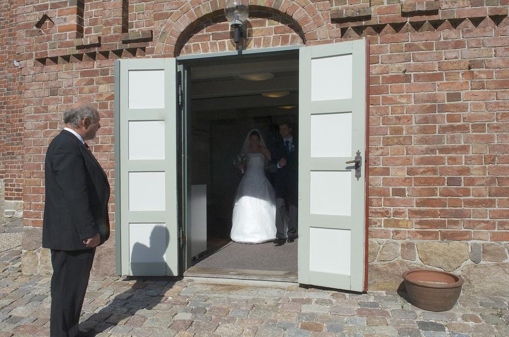 Kuhrt O. Hansen har haft mange hverv ved Blovstrød Kirke. Her tager han som kirketjener imod et netop viet brudepar ved kirkeporten. Det var på datoen 7-9-13. Foto: AOB