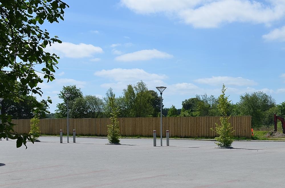 Den store parkeringsplads bag kroen er mod syd-vest begrænset af en støjskærm, som i løbet af et par år bliver en levende, grøn væg. Foto: AOB
