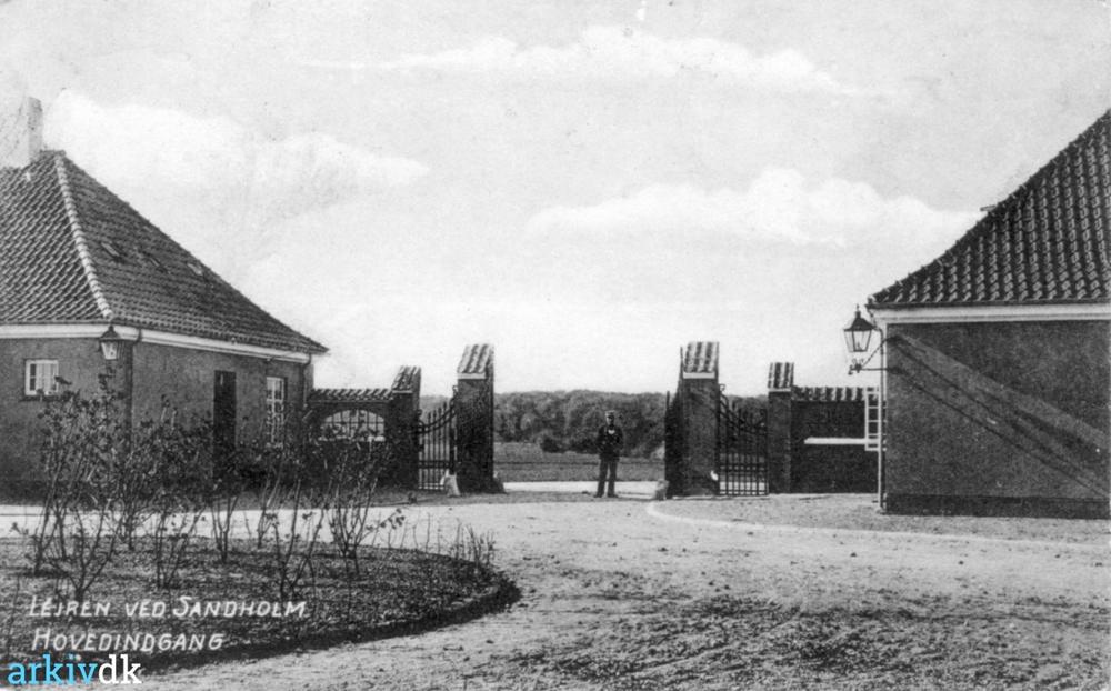 På billedet - som er hentet fra 'arkiv.dk' - ser man den karakteristiske hovedindgang til Sandholm Lejren - set fra gårdspladsen. Postkort fra ca. 1911.