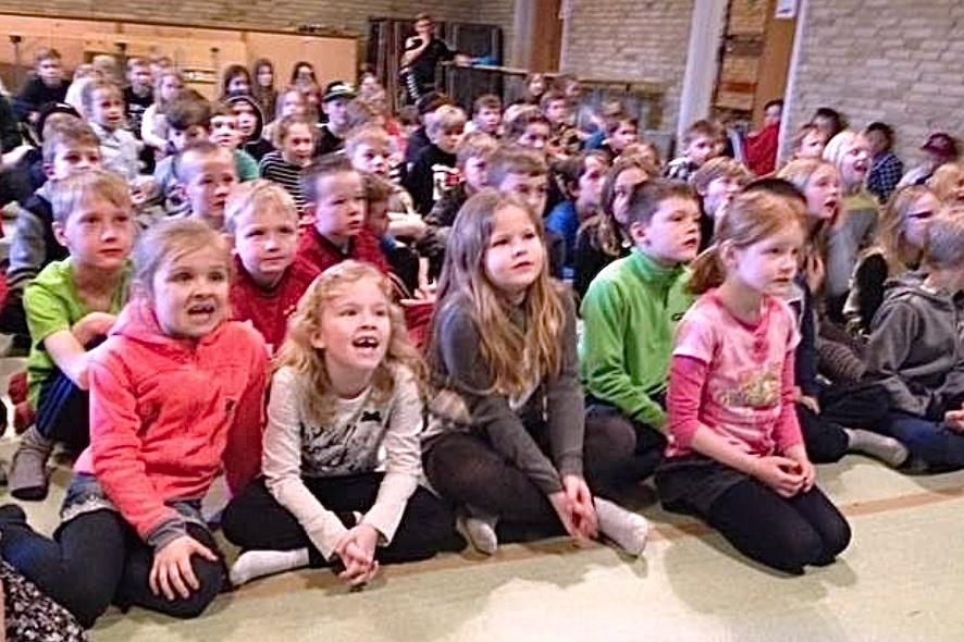 Fra storskærmen i salen kunne eleverne fra 1. til 4. klasse synge med til live-optagelserne på DR Ultra. Foto: Blovstrød Skole