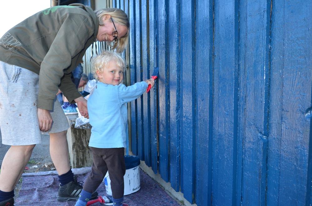 Alle hjalp til med at male hytten spejderblå. Foto. AOB