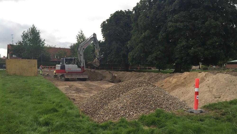 Gravemaskinen på Grønholmen er tæt på at nå målet, som er den brønd, der er markeret med en orange stander. Tilslutningen sker i morgen. Foto: AOB