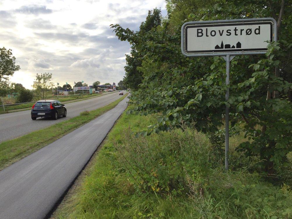 """""""Blovstrød""""-skiltet er nu flyttet ca. 100 meter længere mod syd og markerer, at man nu kører ind i bymæssig bebyggelse og må således kun køre 50 km/t. Foto: AOB"""