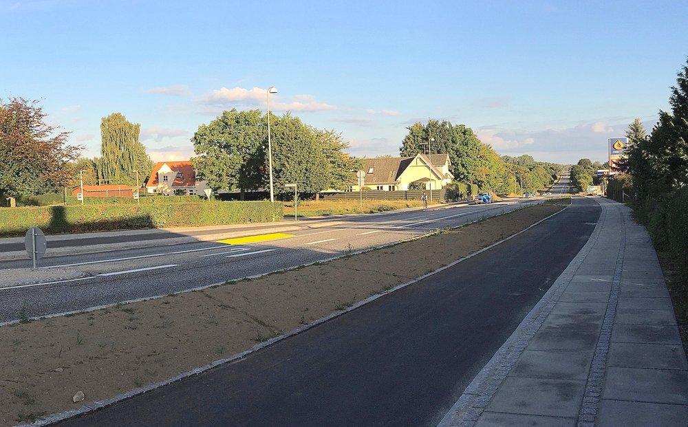 Oprindeligt var busstoppestedet projektmæssigt placeret meget tæt på Blovstrød Byvej (som vist på ovenstående foto, markeret med gult), hvilket bevirkede, at man kunne overhale en holdende bus i venstresvingsbanen, og samtidig kunne bilister fra Blovstrød Byvej ikke overskue den nordfrakommede trafik. Foto:AOB