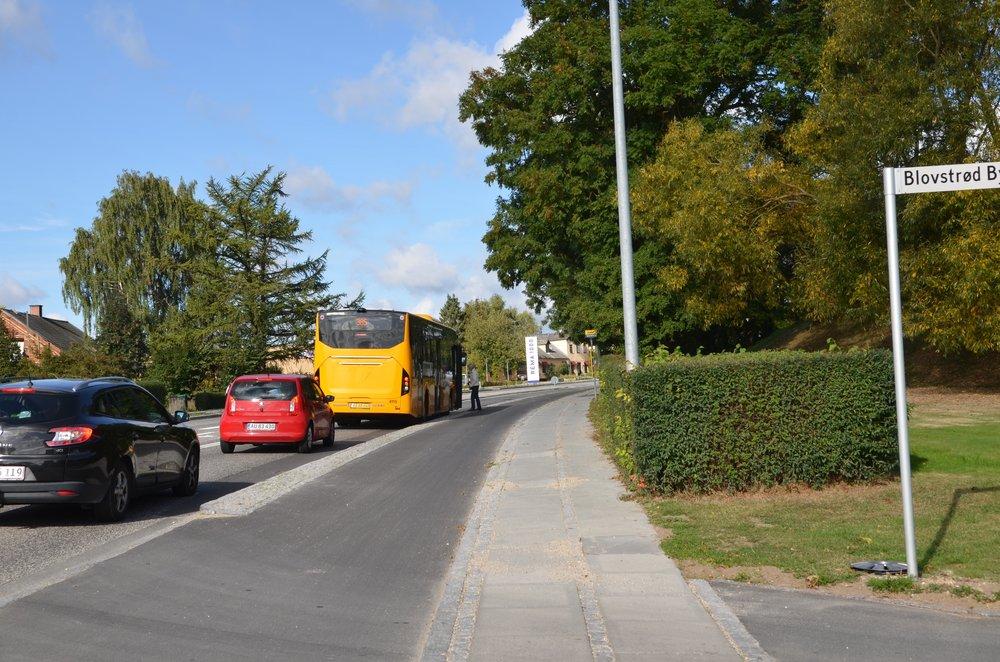 10:22:25: Bussen åbner døren for bus-passageren, og endnu en personbil bremser op for den holdende bus. De holdende biler blokerer for udsynet for de Blovstrød Byvejs-bilister, der skal ud på Kongevejen mod Birkerød.