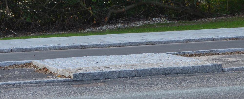 Her er 'synderen' mellem de to parkeringspladser overfor bageren:Den hævede markering mellem de to p-båse er udført af chaussésten og er i niveau med den høje kantsten, hvilket gør, at den ikke kan passeres, hvis man vil skåne sin bildæk. Den bør sænkes ned i plan med asfaltbelægningen. Foto: AOB