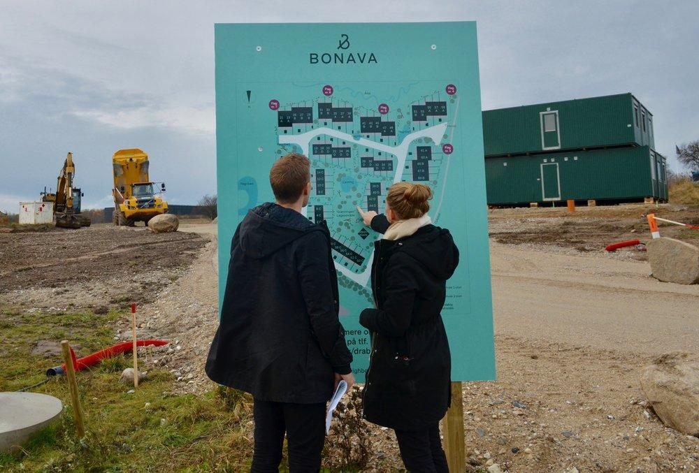 Interesserede studerer oversigtskortet,  som bl.a. angiver Bonava-flagenes placeringer i marken - i alt 8 stk., hvorved man kan se, hvor de enkelte rækkehuse vil blive opført på udstykningen. Foto. AOB