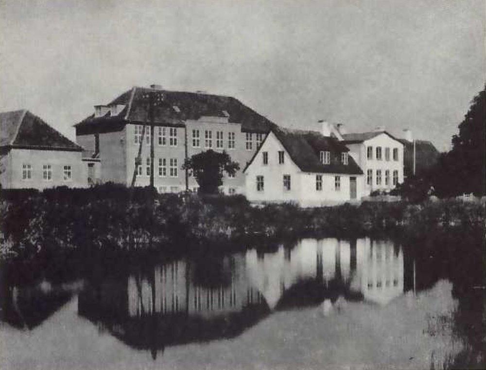 Her ses den gamle stråtækte skolebygning tæt på gadekæret og med den nye skolebygning i baggrunden, som åbnede den 19. august 1938.