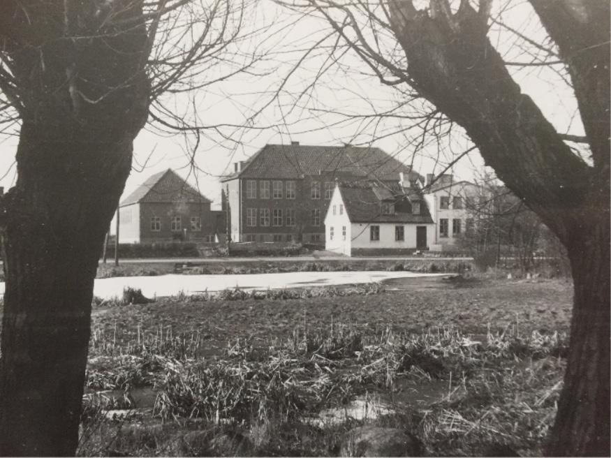 På billedet ses den gamle skole.Det er den hvide, stråtækte bygning, med den nye, store skole bagved.Fotoet er udlånt af LAFAK.