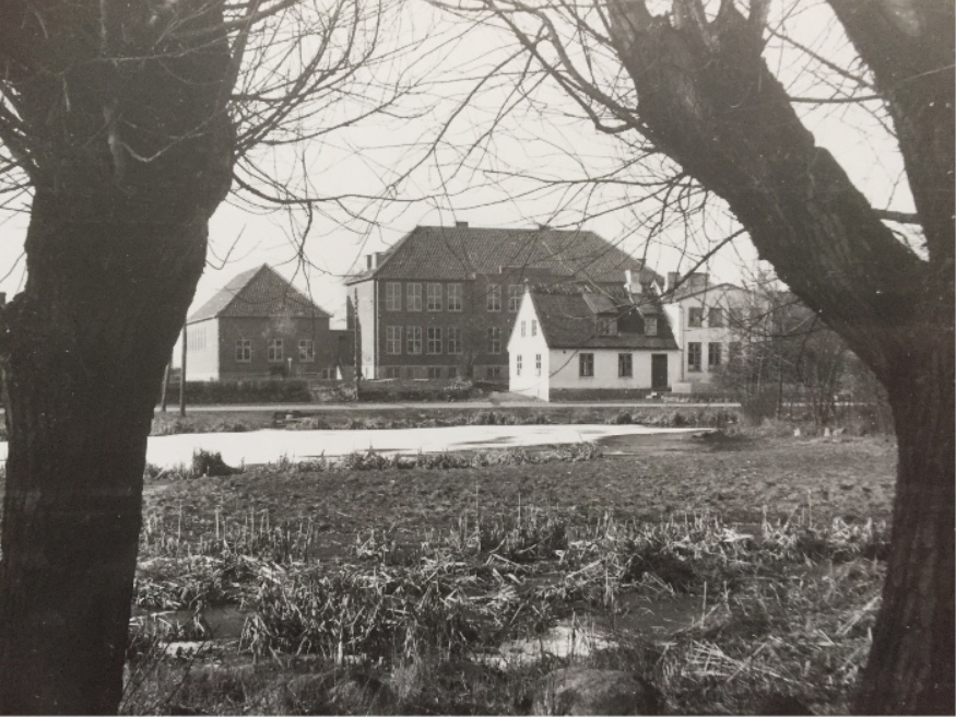 På billedet ses den gamle skole, som er den hvide, stråtækte bygning, med den nye, store skolebygning bagved.Fotoet udlånt af LAFAK.