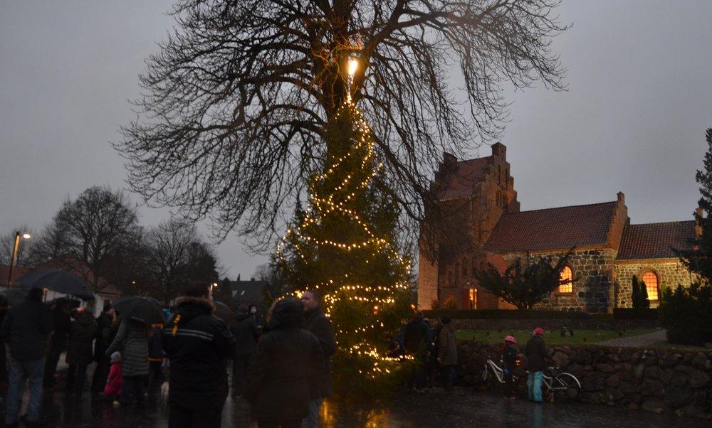 Det regnede pænt, da juletræet skulle tændes på kirkepladsen, men alligevel var der rigtig mange, som var mødt op for at fejre første søndag i advent. Foto: AOB