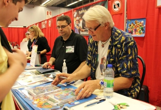 Charles Martinet, signant des autographes.