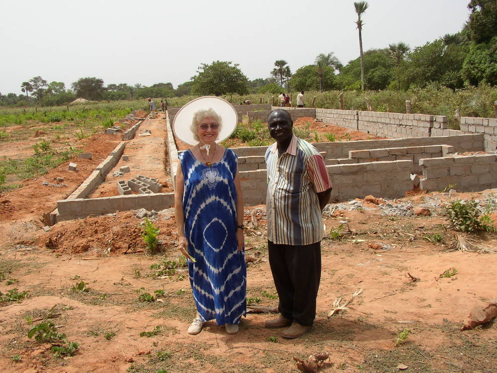Martha Reynolds and a local pastor stand in front of the site of the WAVS School during its first phase of construction.