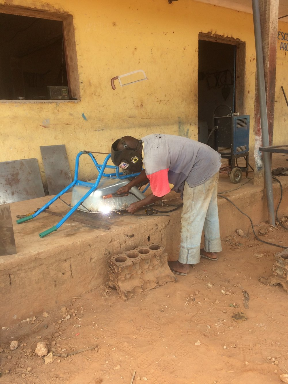 Welding a community member's wheelbarrow.