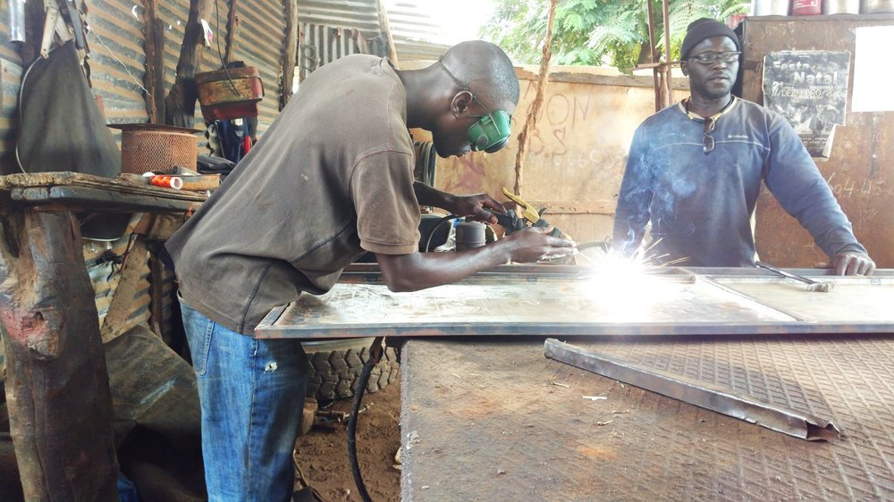 Ciro (right) and Nilton (left) work on welding together a door for a client. Both West Africans studied at the WAVS Vocational School to expand their skill sets so they could take on more types of welding jobs.