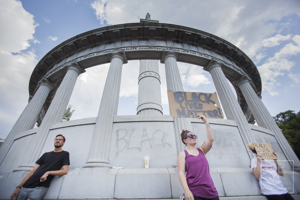 A man and at least three women stand with signs at the foot of the Jefferson Davis statue Thursday.