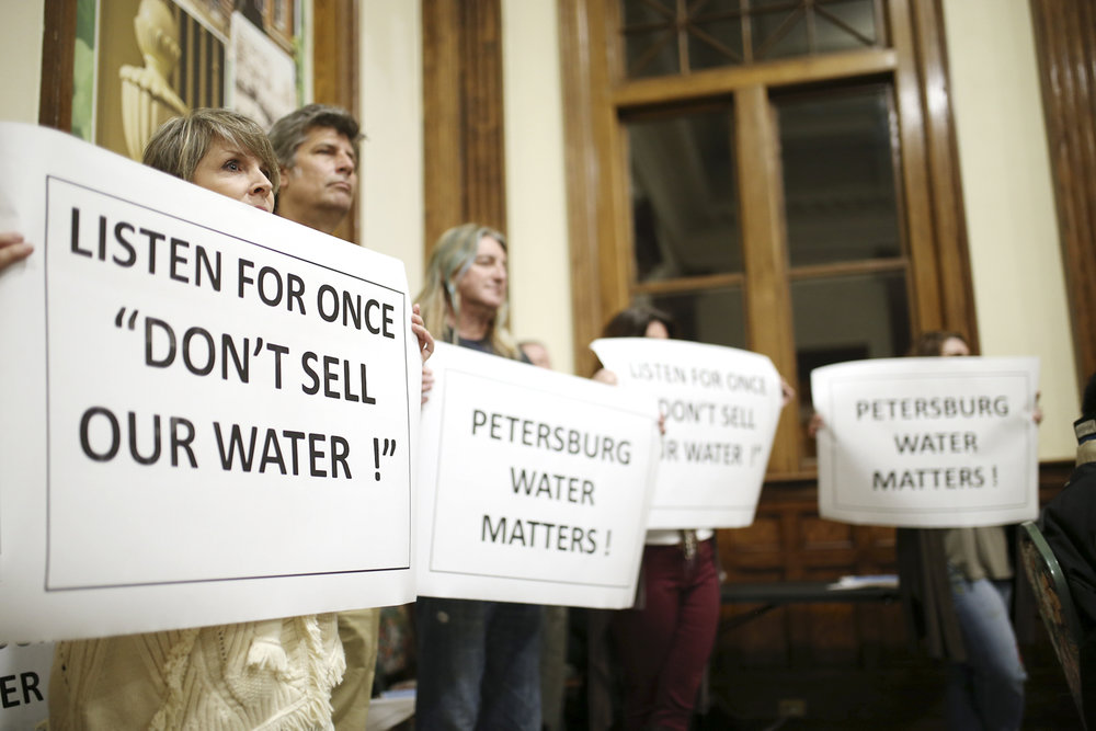 Petersburg residents hold signs urging council members not to privatize the city's water utility during a council meeting at Union Train Station in Petersburg on Tuesday, Feb. 21, 2017. [Scott P. Yates/progress-index.com]