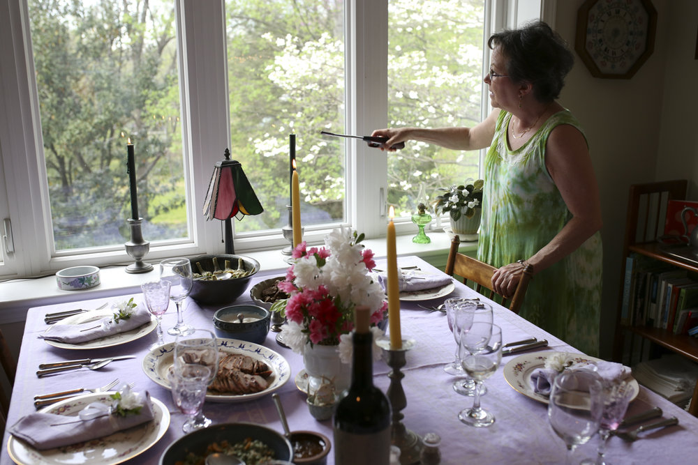 Mom Yates lights a candle at the dinner table before a meal on April 16, 2017, at her home in Roanoke, Va. [Photograph by Scott P. Yates]