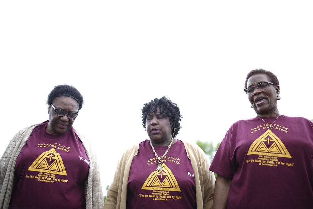 Members of Greater Faith A.M.E. Zion Church in Petersburg, from left, Vivian Jones, Karen Miller, and Pastor Audrey Jones, pray before their march against violence on Halifax Street on Saturday, May 6, 2017. [Scott P. Yates/progress-index.com]