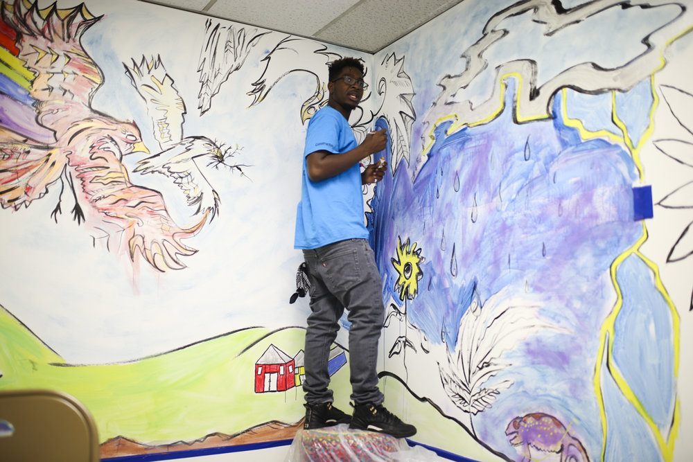 James Bell, from Hopewell, paints a corner of a mural inside a room at Petersburg Kid's Growth building on Wythe Street in Petersburg on Monday, Sept. 11, 2017. [Scott P. Yates/progress-index.com]