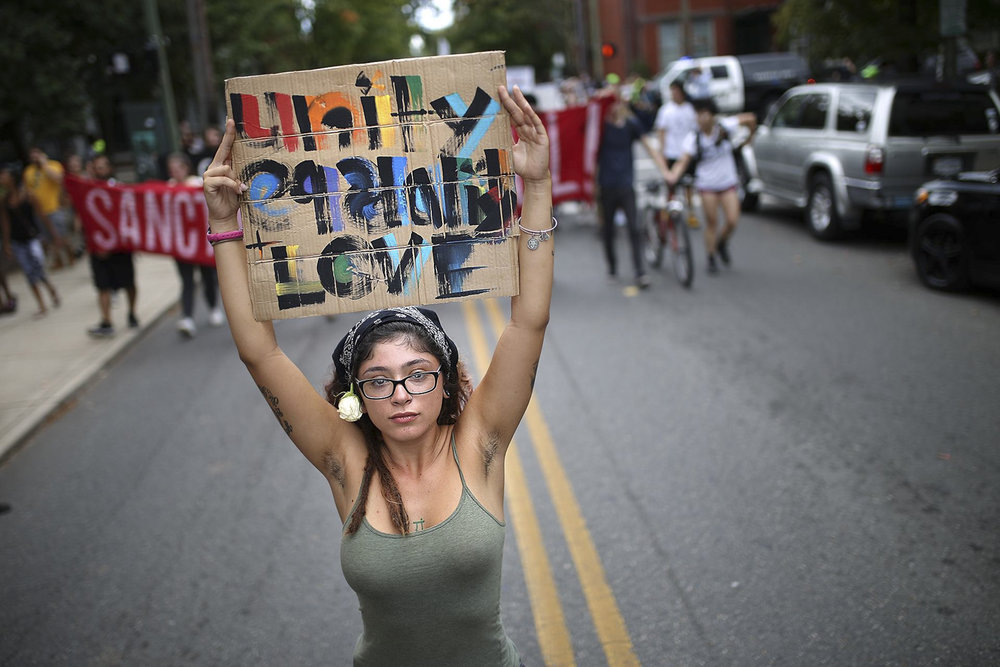 "Jacinda Diaz, from Long Branch, New Jersey, holds a sign that reads, ""Unity, equality, and love"" in front of a large crowd of people protesting against racism, white nationalism, and fascism on N. Lombardy Street in Richmond on Saturday, Sept. 16, 2017. [Scott P. Yates/progress-index.com]"