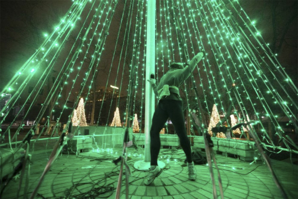 Wayland Anderson of Rockford, a freelance artist, dances inside an illuminated Christmas tree during the Rockford River Lights show on Friday. Dec. 22, 2017. [Scott P. Yates/rrstar.com staff]