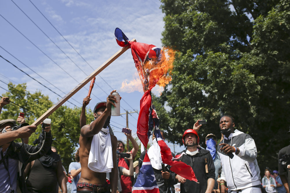Cory Long, a man identified in an article on TheRoot.com, lights a confederate flag on fire after intense street fighting at Emancipation Park in Charlottesville on August 12, 2017. In TheRoot.com article, Long shares his experience of trying to save his friend from a Neo-Nazi beating in a parking garage in while photographers stood by and watched to take pictures. 