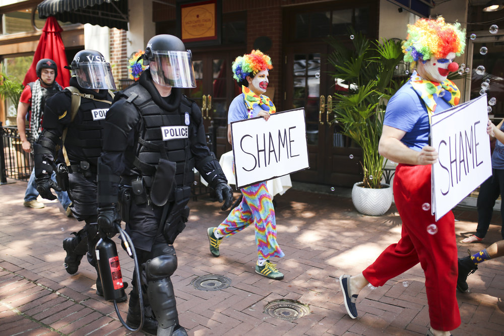 People dressed as clowns walk alongside Virginia State Police officers during an afternoon lull in violent and deadly clashes between Neo-Nazis and counter-protesters in Charlottesville on Saturday, August 12, 2017. [Scott P. Yates/progress-index.com]