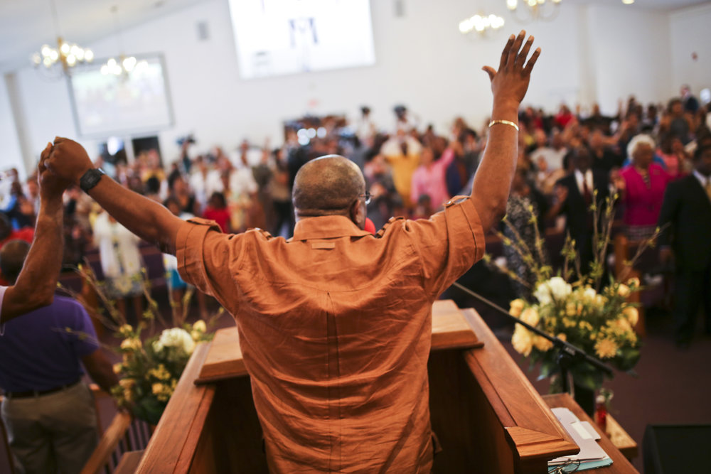 Pastor Alvin Edwards raises his arms in group praise during a Sunday service at Mount Zion First African Baptist Church in Charlottesville, Va., on Sunday, August 13, 2017. [Scott P. Yates for The Wall Street Journal]
